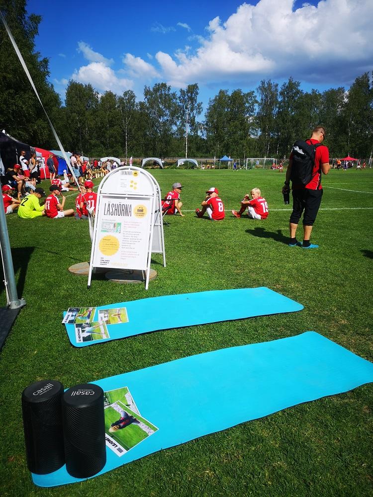 Utanför lästältet ses färggranna träningsmattor, längre bort skymtar man barn i träningskläder.