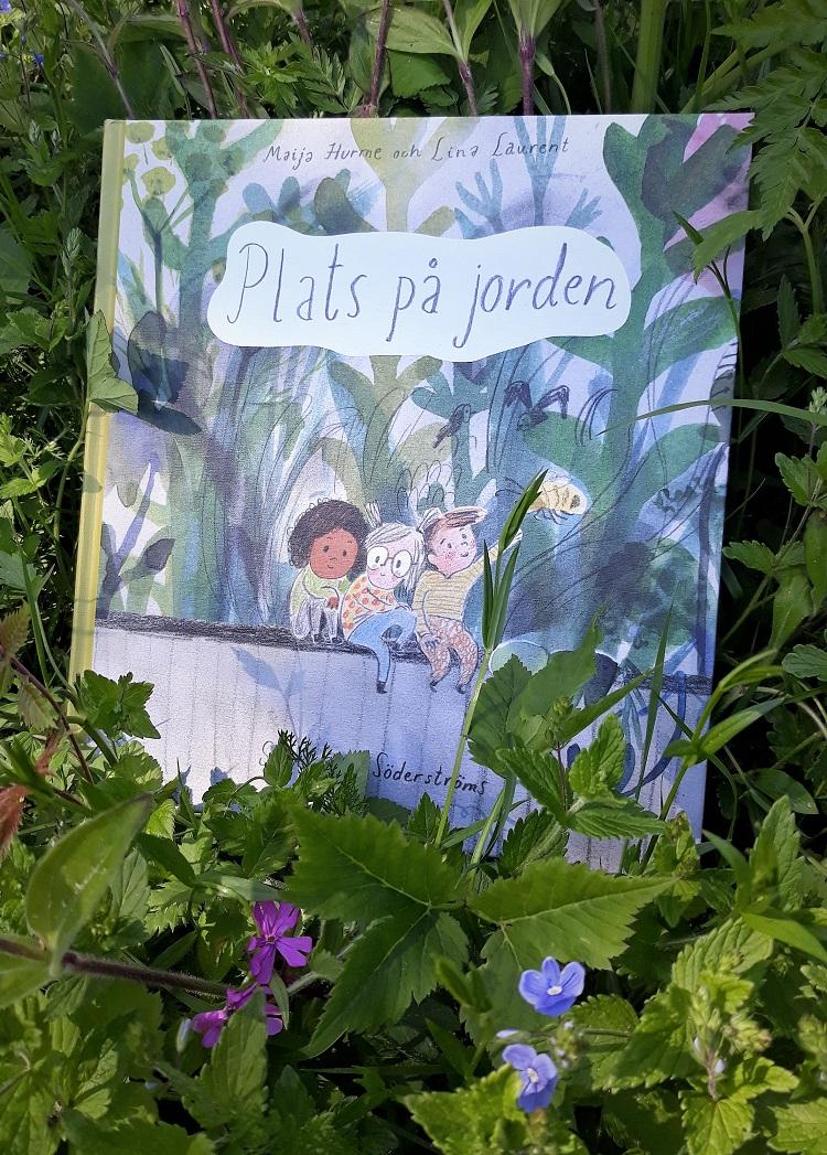 Boken Plats på jorden omgiven av gräs och blommor.