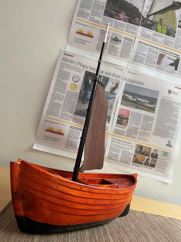En allmogebåt i miniatyr. Bakom den ser man urklipp ur tidningsartiklar som handlar om elevtexter.